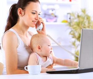 Mother and baby in home office with laptop and telephone ** Note: Visible grain at 100%, best at smaller sizes